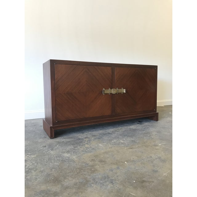 Stunning mahogany sideboard by Tommi Parzinger. Features include brass hardware, three large drawers on the right with a...