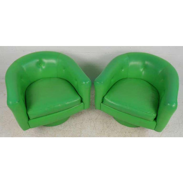 Striking midcentury pair of lime green vinyl chairs with swivel bases. Very comfortable club chairs for any setting....