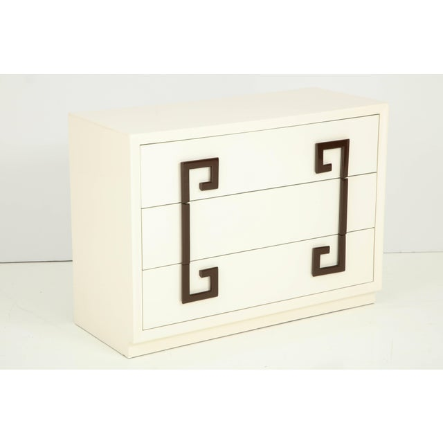 Hollywood Regency chest of drawers in a sophisticated Ivory lacquer with contrasting stylized Greek key pulls in a...
