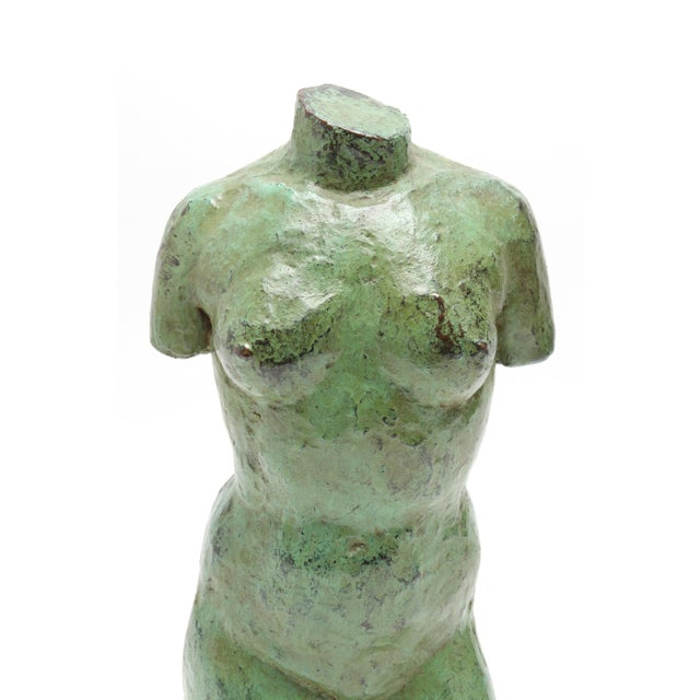 Modern bronze sculpture, depicting a torso of a female nude. The piece has verdigris patina and is mounted to a black...