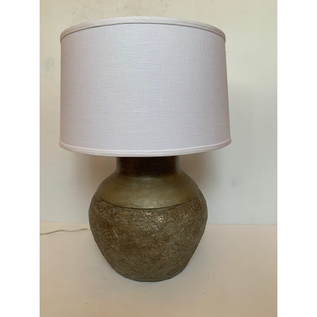 """Great looking large neutral vintage table lamp having embossed metal round base and new canvas shade. Base is 16"""" diameter."""