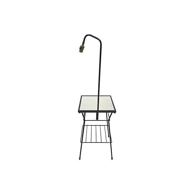 A Mid-Century floor lamp in black iron with an integrated table and wire shelf underneath. The table has a white faux top...