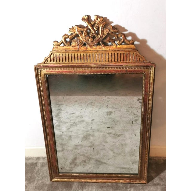 Elegant wooden frame with mirror produced in France in 1750 Louis XVI; on the upper side, we find a rich carved ornament...