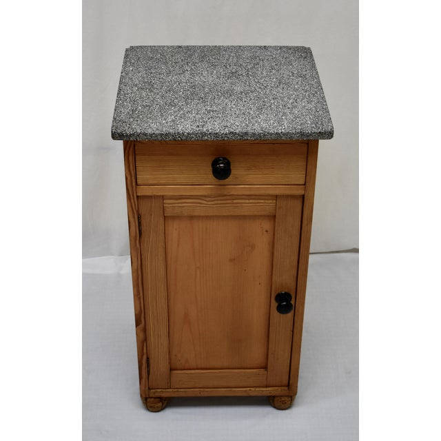 This is a sturdy pine nightstand with a mottled black and white marble top in the usual configuration. The case, with a...