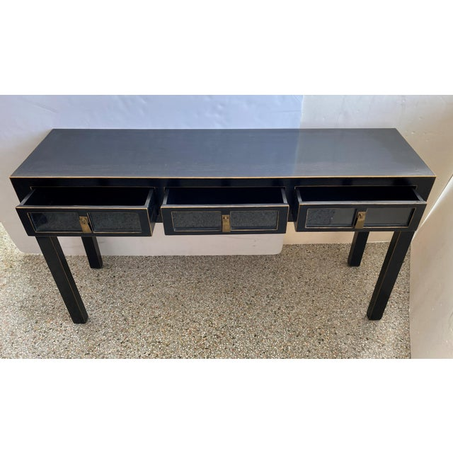 This stylish console table is has been professionally restored in an ebonized finish with hand painted gold edging. Note:...