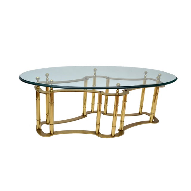 Hollywood Regency Mastercraft Brass Coffee Table with Glass Top. The base shows a well aged patina and the oval heavy...