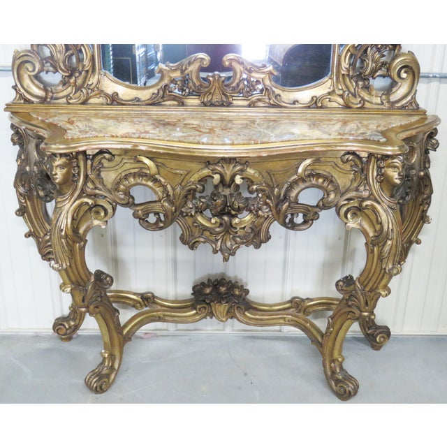 This console with mirror is a beautiful set with gilt carved figures of plumes and flowers and a marble top. There is...
