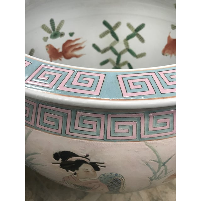 Large pink Asian porcelain fishbowl urn with painted Chinese Royal family scenes, flowers and butterflies. It rests on a...