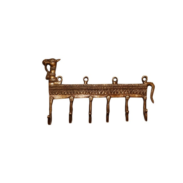 A large bohemian gold brass wall fixture with six hooks. A central bar is cast with a camel head and tail and is decorated...