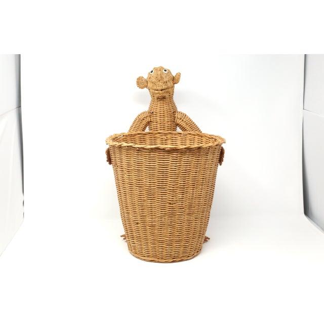 A vintage, wicker wastebasket, held by a figural wicker monkey. Good vintage condition.