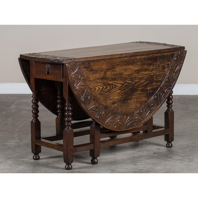 The handsome carving on this antique English oak drop leaf table circa 1885 is a wonderful addition to the striking...