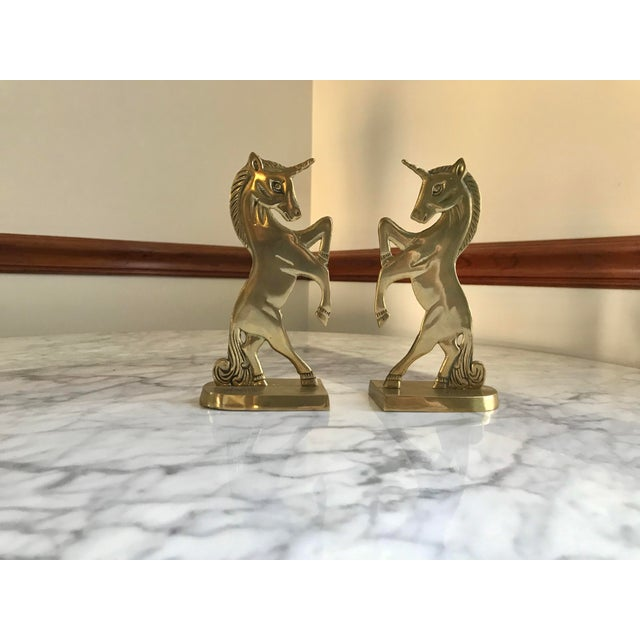"""Pair Mid-Century Brass Unicorn Bookends. In great condition of age and usage. Dimensions: Each Bookend- 3.5""""W x 2.5""""D x..."""
