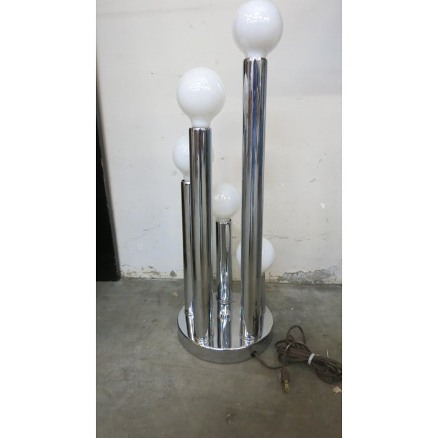 Table lamp with multiple cylindrical stacks topped with globe lights. Multiple switches. The varying height of cylinders....