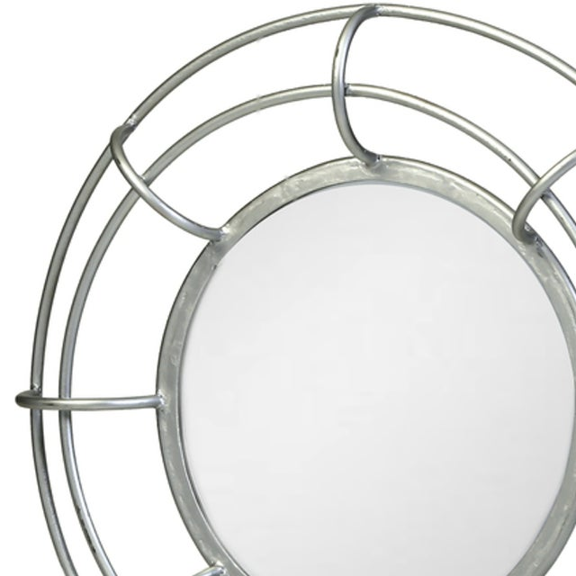 A slim, hand-forged metal frame with a silver-leaf finish encircles this round mirror for a subtle statement.