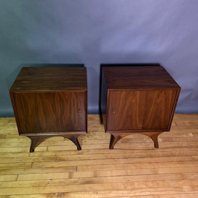 Classic pair of American mid-century walnut nightstands with simple square fronts edged in a tapered trim over a flared-...
