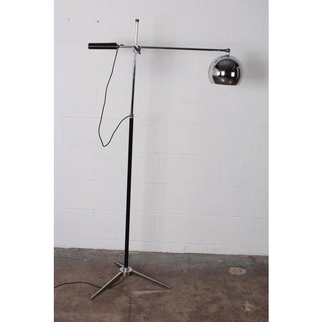 An early Arteluce single arm articulating floor lamp with tripod base and leather wrapped handle.