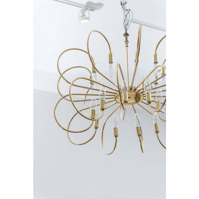 Polished brass twelve-arm chandelier.