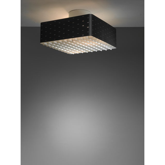 A Paavo Tynell model 9068 flush mount ceiling lamp for Idman. The lamp is made of black lacquered metal with twin dot...