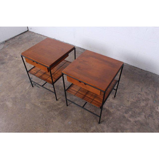 A pair of iron framed nightstands with bamboo shelf. Designed by Paul McCobb for Winchendon.