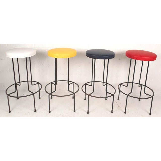 This beautiful set of vintage modern bar stools feature sturdy wrought iron bases with unique bent rod legs and circular...