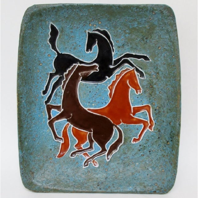 Artisan-created Tuscan-style ceramic footed catchall accented with three brown-glaze horses on a turquoise, blue and...