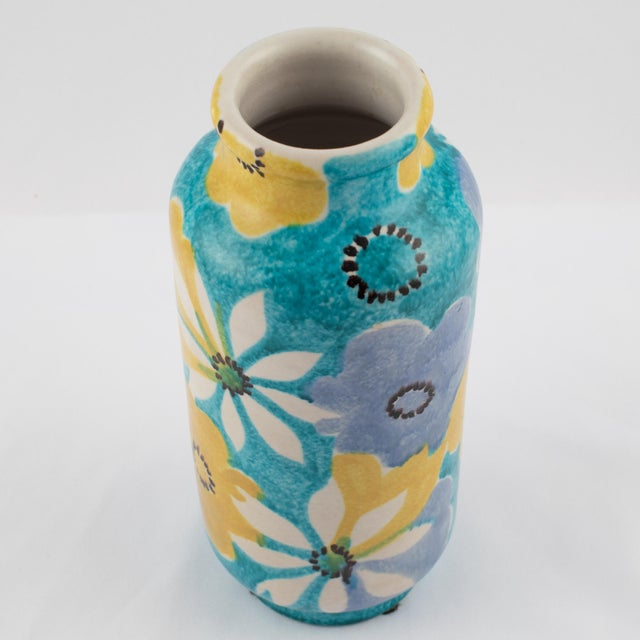 Lovely cylindrical vase glazed with hand painted blue, white and yellow flowers on an aqua background, by Italian...