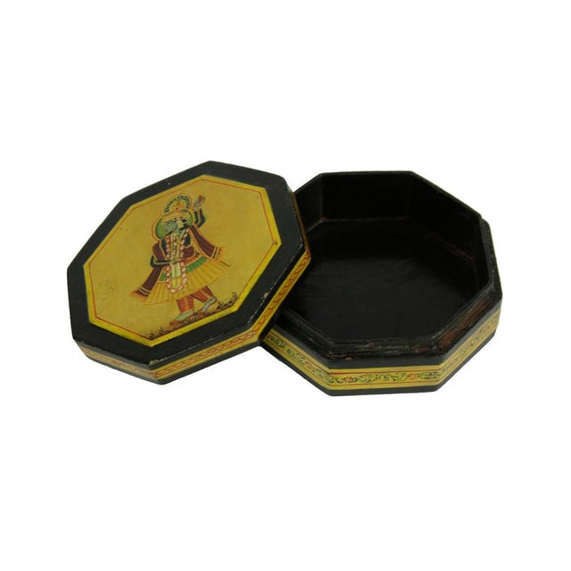 This vintage wooden storage box is profusely decorated in golden vines and foliate motifs, with the top depicting a scene...