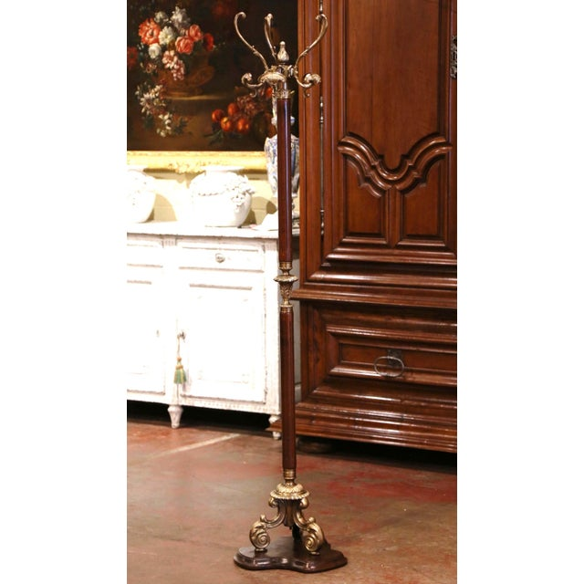 This antique carved fruit wood and brass hall tree was crafted in France, circa 1920. Standing on a carved triangle...