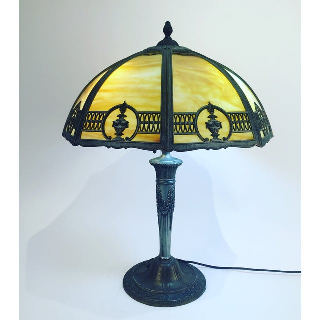 Beautiful rare Antique slag table lamp with magnificent metal work on the detail of the shade and base. Have 3 light bulbs...