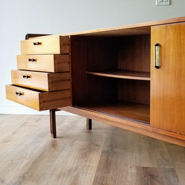 A Mid-century modern credenza made in Italy. This piece features bypass constructed legs, dovetail drawers, metal handles,...