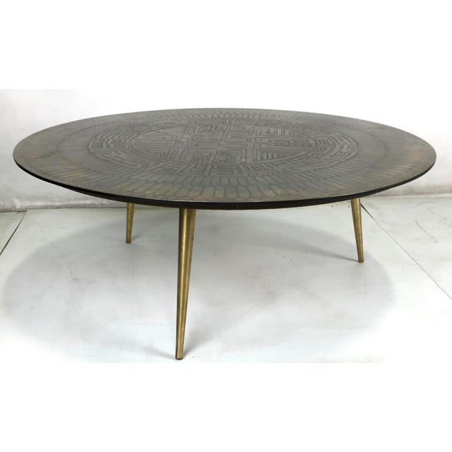 Mid-Century etched bronze coffee table raised on three tapering brass legs. The deeply etched top has a wonderful...