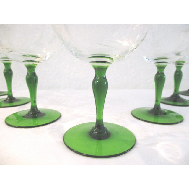 Lovely set of seven Emerald-green stemmed wine glasses featuring a delicate etched floral design around perimeter of clear...