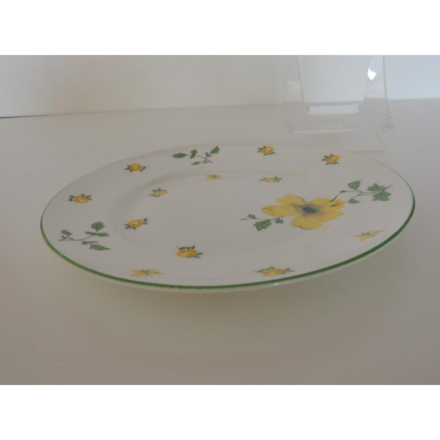 "White china plate with yellow flowers, green leaves and gold accent. Size: 8.5""D x. 25""H"