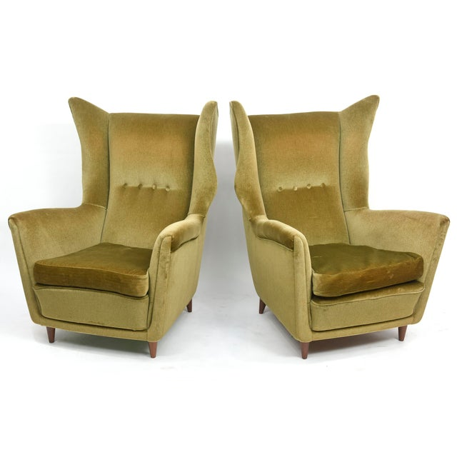 Large and imposing pair of Italian modern lounge chairs with high backs and wings on round tapering legs.