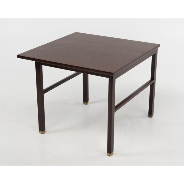 A square cantilevered walnut end table by Edward Wormley for Dunbar, c. 1960's. Features cantilevered top and brass feet....