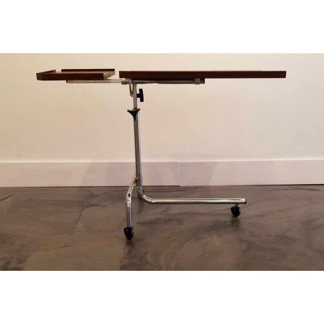 A Danish Modern adjustable table made of rosewood and polished chrome. Top tilts 90 degrees and has height adjustment from...