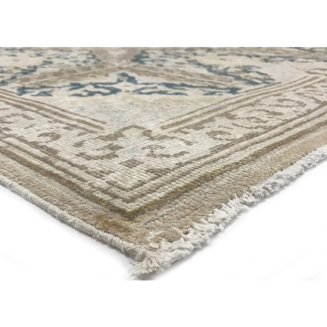 This vintage, distressed Persian rug was hand woven in Iran in the mid 1940's. The colors and pattern have been hand...