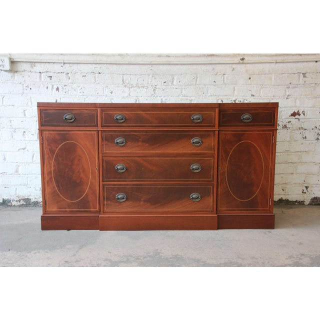 An outstanding vintage inlaid mahogany sideboard or buffet by Baker Furniture. The sideboard features gorgeous flame...