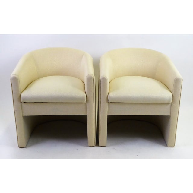 Wonderful pair of 1960s barrel back tub chairs newly upholstered in a creamy white woven fabric with gold threading....