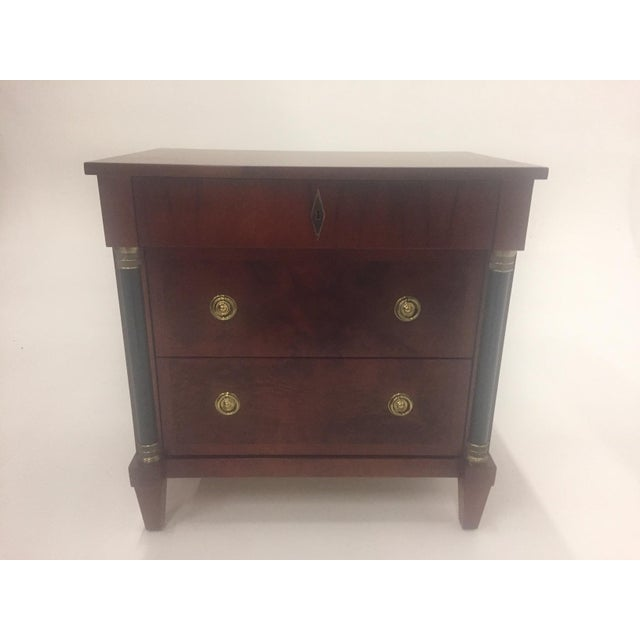 A Classic mahogany Empire small commode having ebonized columns and handsome brass hardware including decorative...