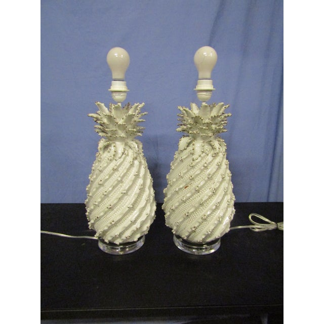 Stunning Pair of Ceramic Lamps on a Lucite base. The Pair have exceptional detail, white glaze and drum shades . The Pair...