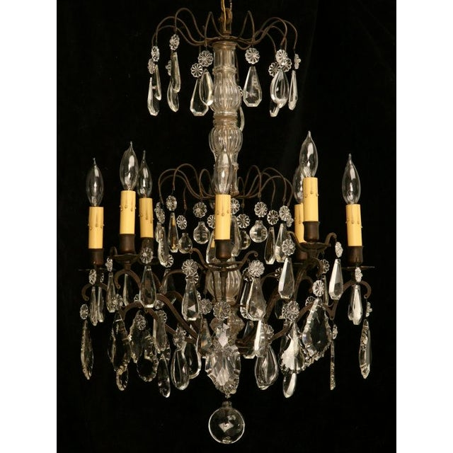 Exquisite restored French 1920's 8 light chandelier with a bronze frame and many polished hand-cut crystal prisms. A...