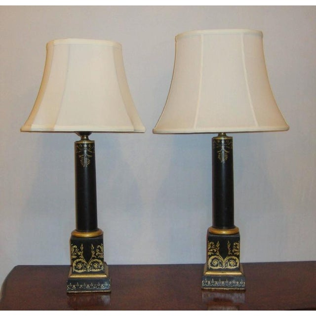 A pair of ebonized lamps in a column style, on a square metal bases. Gilded, elegant, floral design on all four sides of...