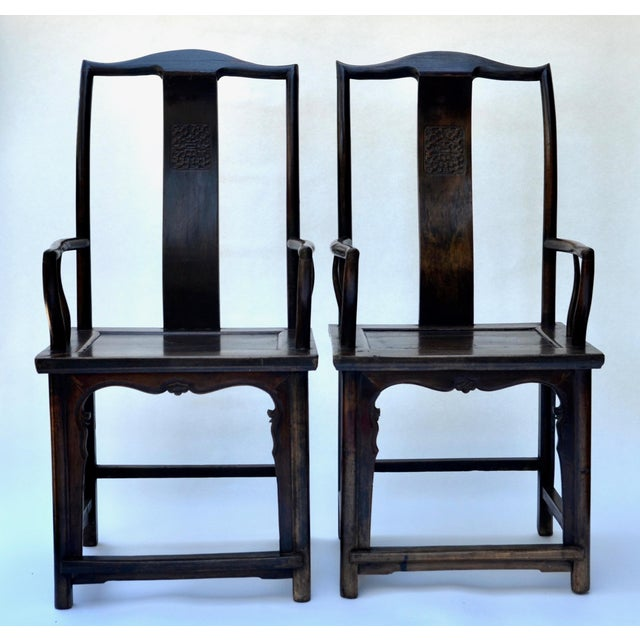 A fine pair of 19th century classic yoke-back elm armchairs with beautiful silk cushions, in fluid curves and an elegant...