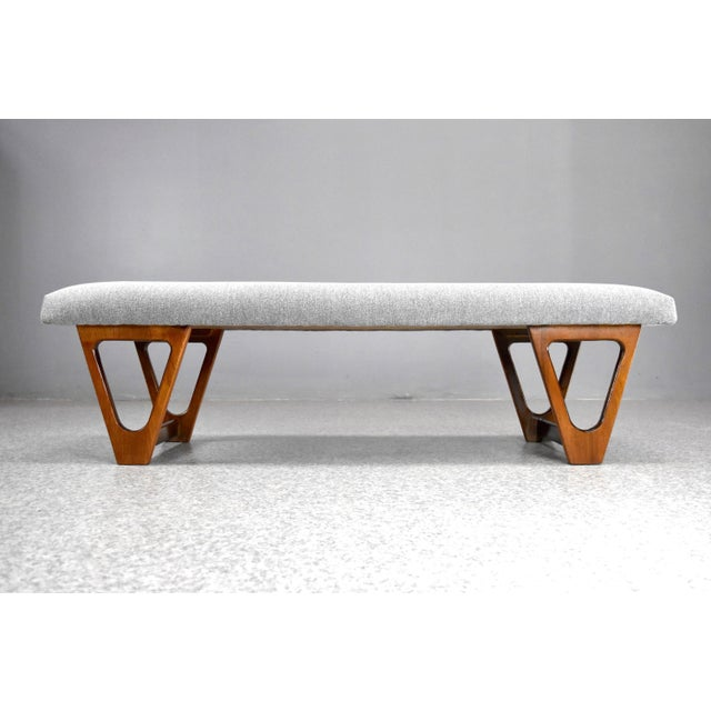 Timeless mid-century modern upholstered bench with sculpted walnut frame, C1960s. Ideal extra seating option for use in an...