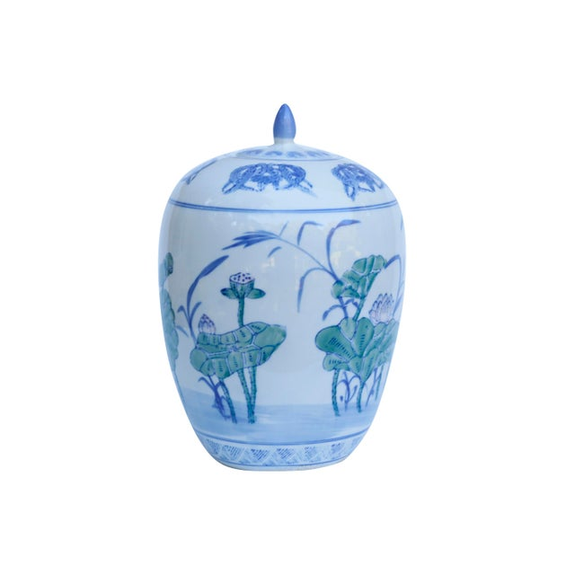 A Chinoiserie ceramic ginger jar with inset lid. Decorated with hand painted lotus leaves and flowers with furled leaves...