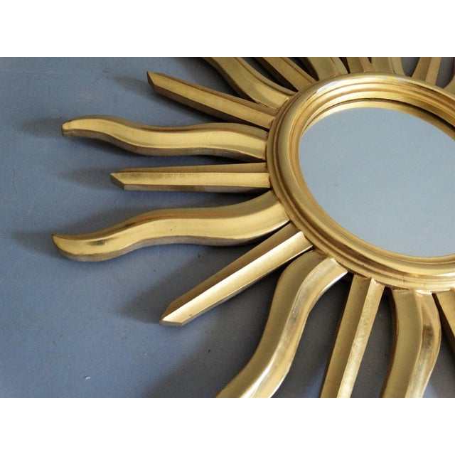 A Mid Century Italian sunburst mirror. It is bright giltwood with lovely undulating rays and retains the original mirrored...