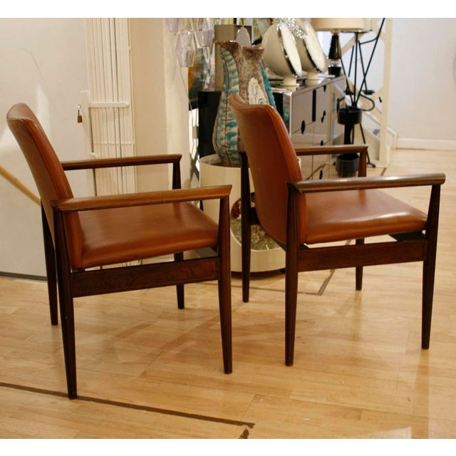 A pair of Diplomat Chairs, brown leather upholstery on a rosewood structure designed by Finn Juhl c.1960s
