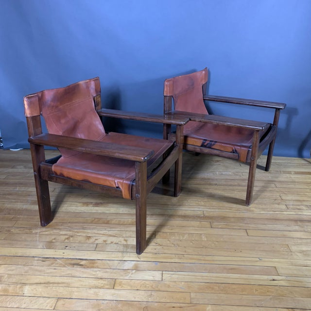 Classic Scandinavian Modern pair of paddle-arm lounge chairs made with solid dark-stained oak frames wrapped in a perfect...