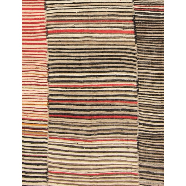 This gorgeous traditional Persian Kilim wool rug is woven in shades of orange, red, yellow, black, cream, and grey....